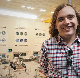 Thomas Connor with Mars Rover in background in a large, white room